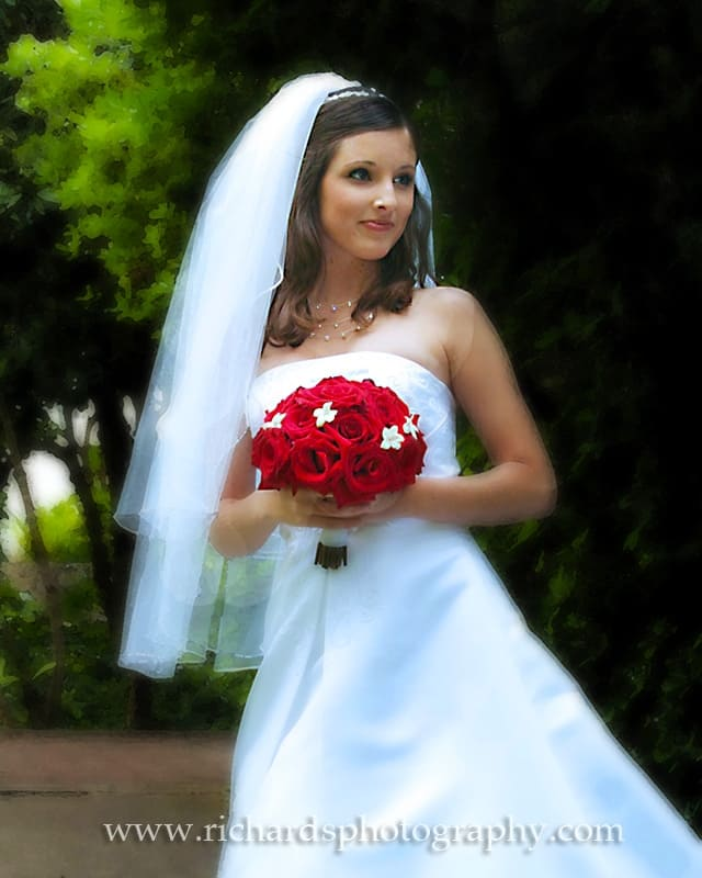 photo of a wedding bride with her bright red bouquet