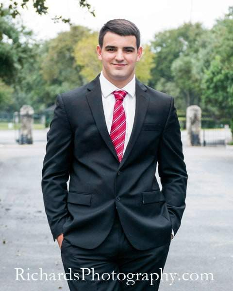 boy in suit and tie standing senior portraits