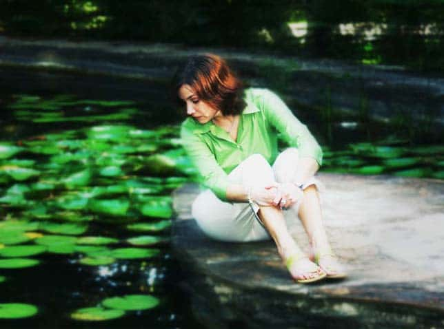 Portrait of a girl looking into a water pond with lillies