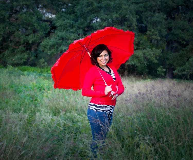 High School Senior Portrait of Girl Standing in a Field With Red Umbrella