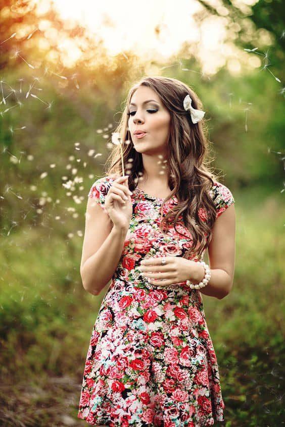 girl wearing dress blowing flowers petals