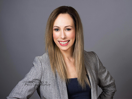 woman smiling for portrait session wearing gray blazer