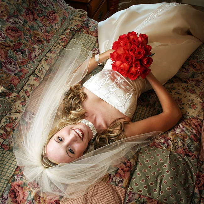 bride with bouquet laying on bed