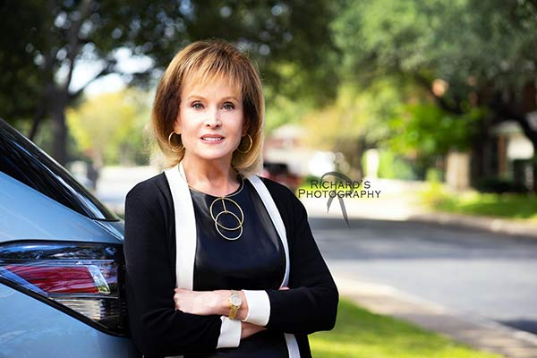 female realtor arms folded portrait outside
