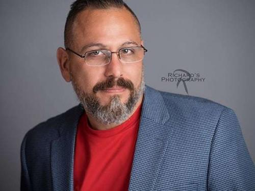 actor headshot san antonio wearing gray suit and glasses