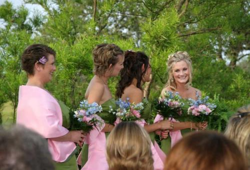 Photo of maid of honor smiling at other bridesmaid at wedding in Fredericksburg Texas