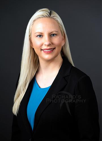 woman headshot blonde hair black jacket